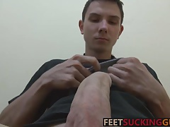 Hung twink Eryk is playing with his feet and big uncut cock